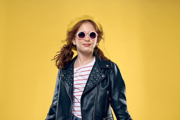 Vrolijk meisje in zonnebril en hoed studio gele mode