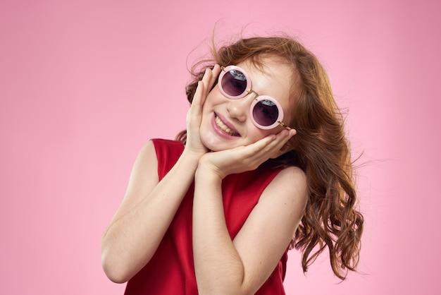 Vrolijk meisje jeugd donkere glazen rode jurk levensstijl roze achtergrond