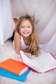 Vrolijk meisje leesboek in een handgemaakte schuilplaats