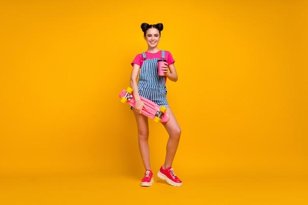 Vrolijk meisje met bord drinken latte geïsoleerd op gele kleur achtergrond
