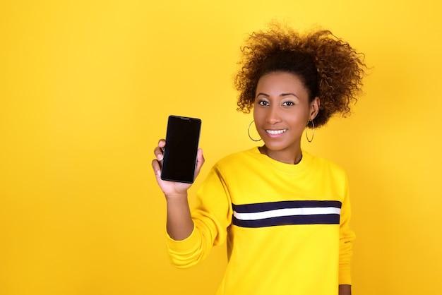 Vrolijk meisje met een donkere huid in een geel sweatshirt demonstreert haar smartphonescherm en glimlacht