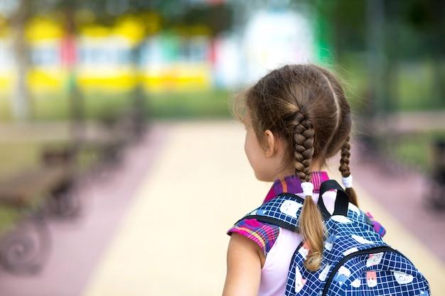 Vrolijk meisje met een rugzak en in een schooluniform op het schoolplein terug naar het frame. terug naar school, 1 september. een blije leerling. basisonderwijs, basisschool. weg naar het leven, naar kennis