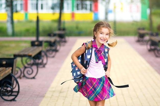 Vrolijk meisje met een rugzak en in een schooluniform op het schoolplein. terug naar school, 1 september. een blije leerling. basisonderwijs, basisschool. portret van een student