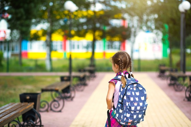 Vrolijk meisje met een rugzak en in een schooluniform op het schoolplein