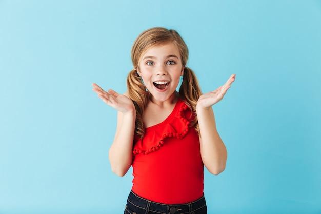 Vrolijk meisje met een zwempak dat geïsoleerd over de blauwe muur staat en plezier heeft