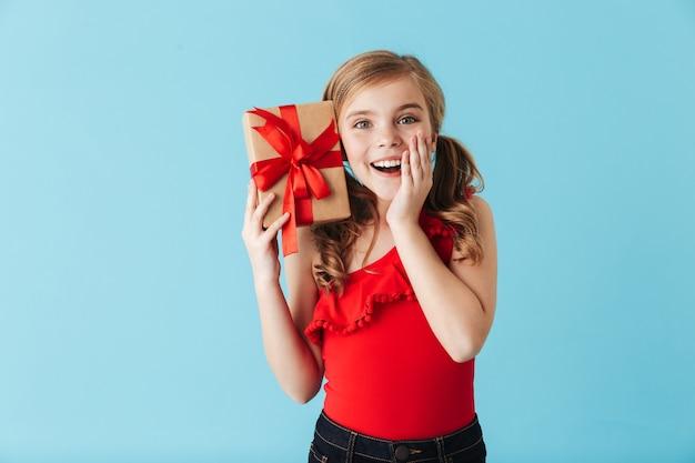 Vrolijk meisje met een zwempak dat geïsoleerd over een blauwe muur staat en een geschenkdoos toont