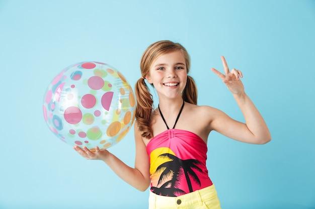 Vrolijk meisje met een zwempak dat geïsoleerd over een blauwe muur staat en een strandbal vasthoudt