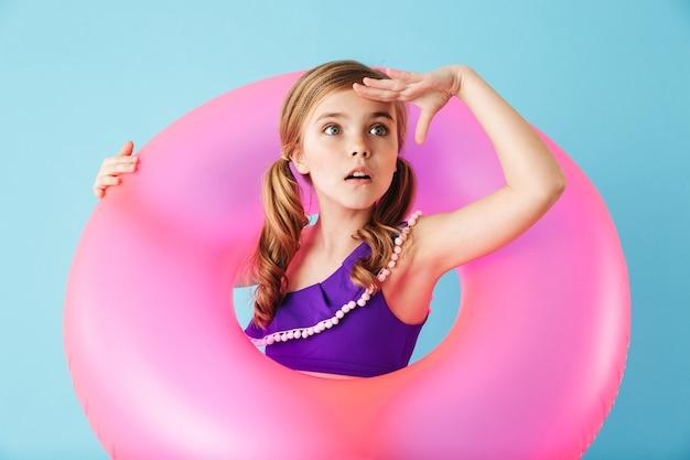 Vrolijk meisje met een zwempak dat geïsoleerd over een blauwe muur staat en met een opblaasbare ring speelt