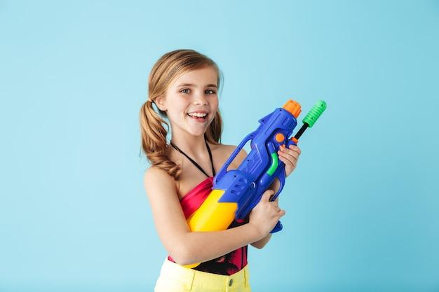 Vrolijk meisje met een zwempak dat geïsoleerd over een blauwe muur staat en met een waterpistool speelt
