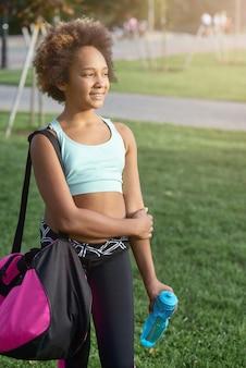 Vrolijk meisje met fles water die op straat staat