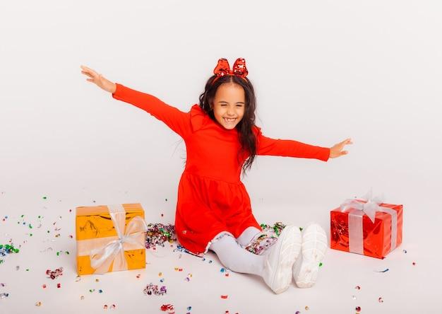 Vrolijk meisje met geschenkdoos op feestje met confetti die over haar heen valt. verjaardag of nieuwjaarsviering