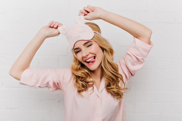 Vrolijk meisje met golvend haar dansen op een witte muur. schattige dame in oogmasker met plezier in de ochtend.