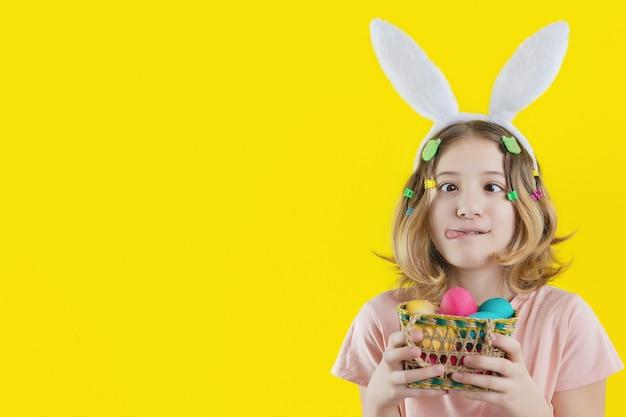 Vrolijk meisje met grappig gezicht en konijnenoren op haar hoofd met mandje met kleurrijke eieren in haar handen. paasvakantie