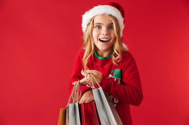 Vrolijk meisje met kerstmuts geïsoleerd staan, met boodschappentassen