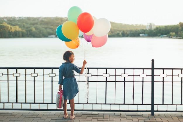 Vrolijk meisje met kleurrijke ballonnen en kinderachtige koffer