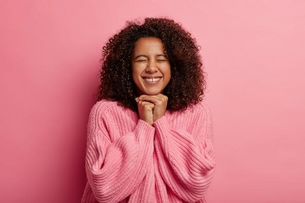 Vrolijk meisje met knapperig haar, houdt de handen bij elkaar onder de kin, blij om het doel te bereiken, heeft de ogen dicht, glimlacht breed geïsoleerd op roze studiomuur