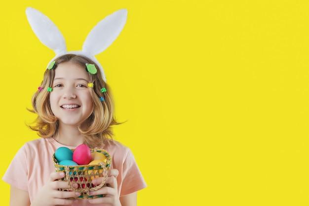 Vrolijk meisje met konijntjesoren op haar hoofd en mand met kleurrijke eieren in haar handen. paasvakantie