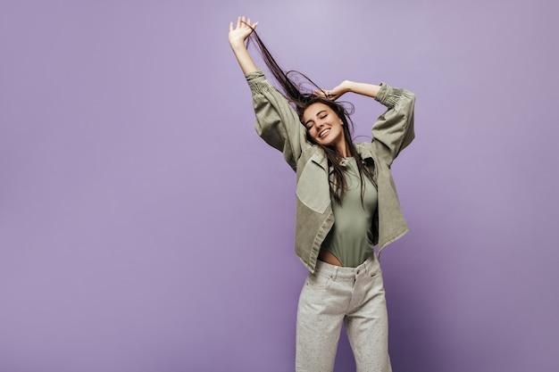 Vrolijk meisje met lang donkerbruin haar in cool t-shirt, modern olijfjasje en wijde broek glimlachend en poserend met gesloten ogen