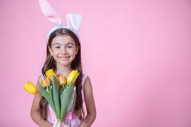 Vrolijk meisje met paashaas oren glimlacht en houdt een boeket tulpen in haar handen op een roze studio