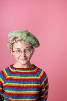 Vrolijk meisje met regenboogtrui en groene baret op een roze achtergrond