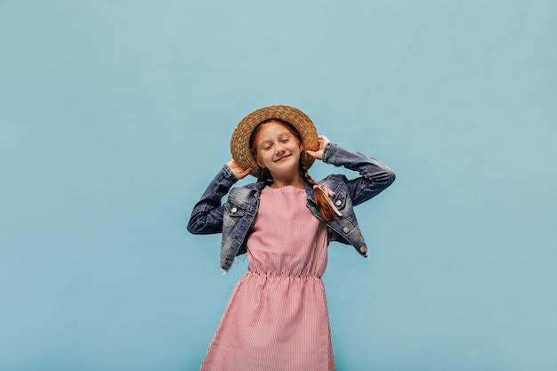 Vrolijk meisje met rood haar in gestreepte zomerjurk, trendy denim en strohoed glimlachend met gesloten ogen op blauwe geïsoleerde muur