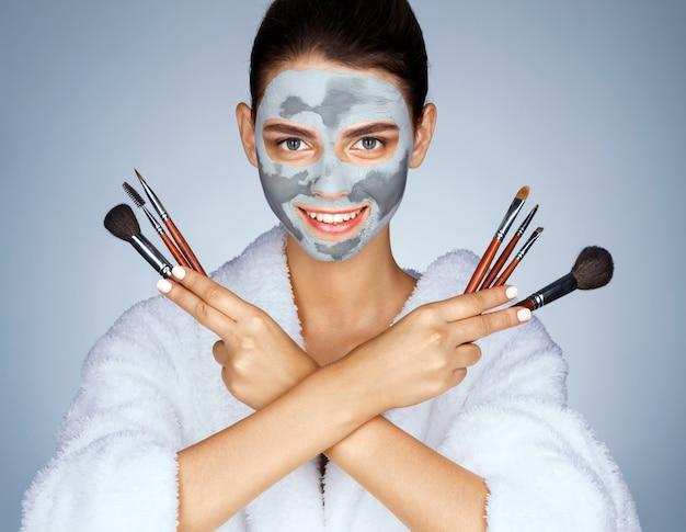 Vrolijk meisje met set make-up kwasten