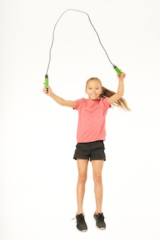 Vrolijk meisje met springtouw springen in studio