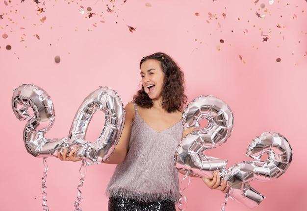Vrolijk meisje met zilveren folieballonnen in de vorm van cijfers