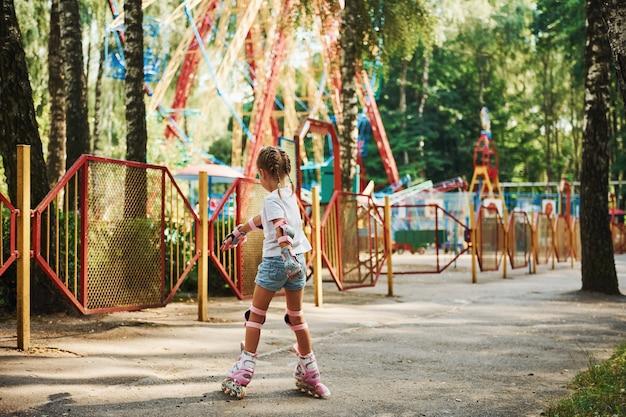 Vrolijk meisje op rolschaatsen heeft een goede tijd in het park in de buurt van attracties