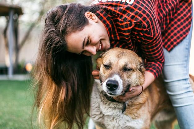 Vrolijk meisje speelt met haar hond in de tuin van het huis in het voorjaar