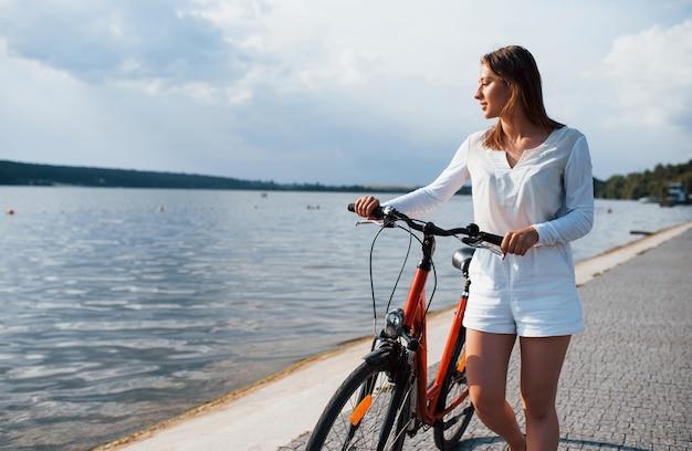 Vrolijk meisje staat met fiets op het strand in de buurt van het meer op zonnige dag.