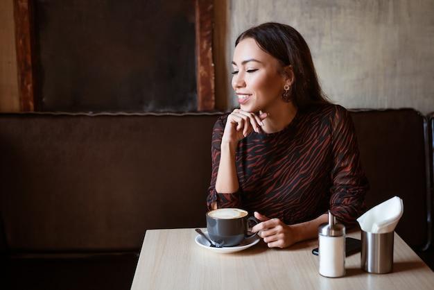 Vrolijk meisje van blanke etniciteit zit aan een tafel in een café met een kopje koffie mooie jonge ...