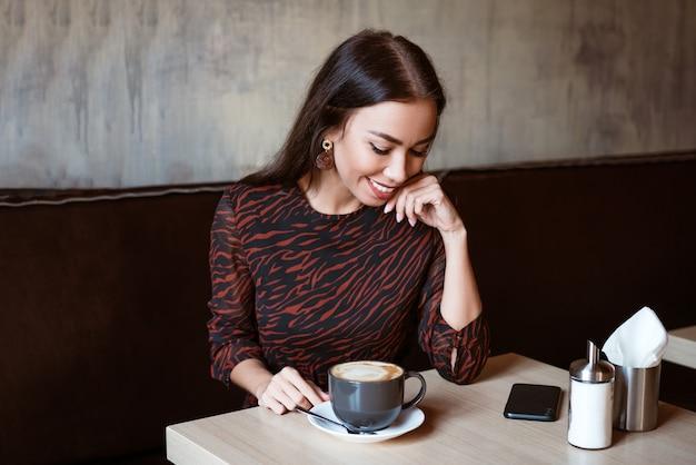 Vrolijk meisje van kaukasische etniciteit zit aan een tafel in een café met een kopje koffie mooie jonge brunette vrouw met een mooie make-up en een whitetoed glimlach glimlachen