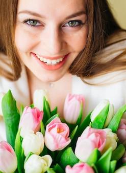 Vrolijk meisje verheugt zich in een groot boeket delicate tulpen. zonnige lentemorgen. natuurlijke schoonheid. lente bruid boeket. fijne vrouwendag.
