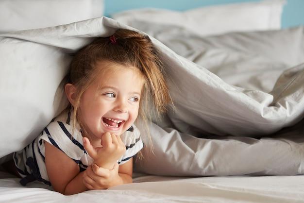 Vrolijk meisje verstopt onder de lakens