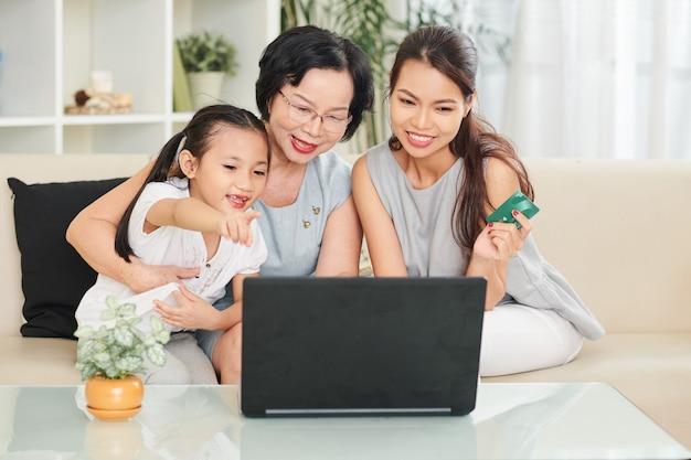 Vrolijk meisje vraagt moeder en grootmoeder om haar speelgoed of boek te kopen in de online winkel als ze op een geopende laptop zitten