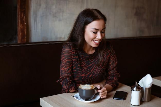 Vrolijk meisje zit aan een tafel in een café met een kopje koffie