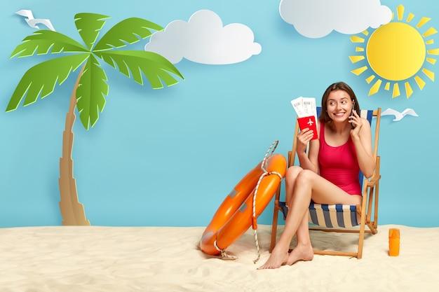Vrolijk meisje zonnebaadt op het strand, poses op de ligstoel, spreekt via mobiele telefoon, paspoort met kaartjes houdt, geniet van zomervakantie