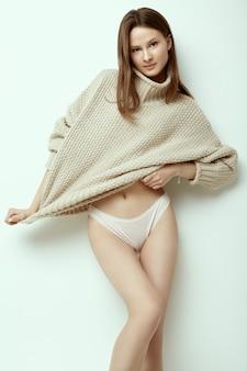 Vrolijk mode hipster meisje in comfortabele sweater op studioachtergrond