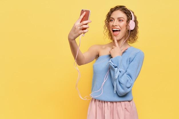 Vrolijk model luisteren naar muziek met een koptelefoon, glimlachend.