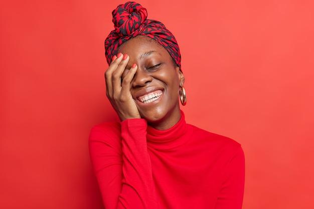 Vrolijk model met donkere huidskleur houdt hand op gezicht glimlacht breed toont witte tanden lacht om iets drukt positieve emoties uit draagt vrijetijdskleding in één toon met
