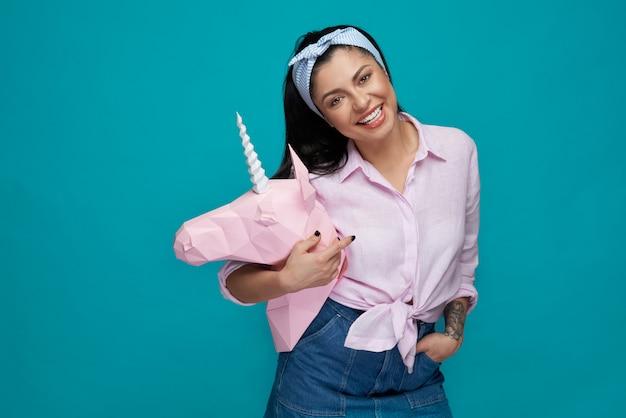Vrolijk model poseren, roze papieren eenhoorn kop houden.