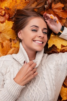 Vrolijk model van een jonge stijlvolle vrouw met blauwe ogen met een aantrekkelijke glimlach in een stijlvolle gebreide witte trui tegen een achtergrond van oranje blad. gelukkig meisje ligt op gouden bladeren in het park.