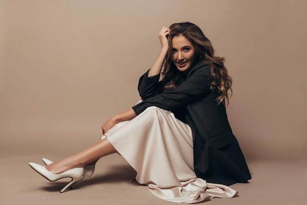 Vrolijk model zittend op de vloer, gekleed in een modern oversized zwart jasje en een romige lange jurk, schoenen met hoge hakken aan haar voeten. krullend kapsel en make-up
