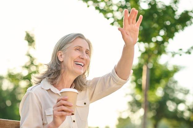 Vrolijk moment. gelukkig verheugende volwassen grijsharige vrouw met koffie groet gebaren met hand in park op zomerdag