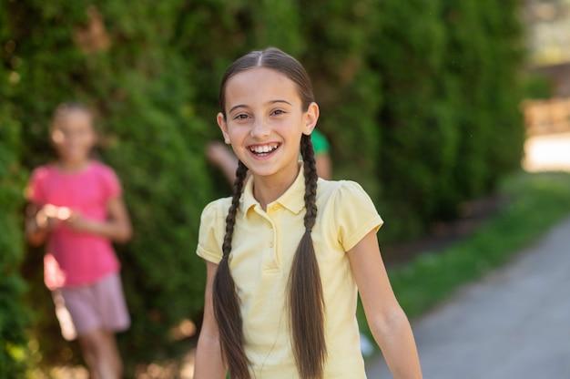 Vrolijk moment. lachend donkerharig meisje met staartjes in lichte tshirt en vrienden achter in park in de buurt van struiken