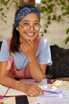 Vrolijk mooi gemengd ras meisje heeft een perfecte charmante glimlach, toont witte tanden, draagt een blauwe hoofdband op het hoofd, bezig met het schrijven van de nodige notities