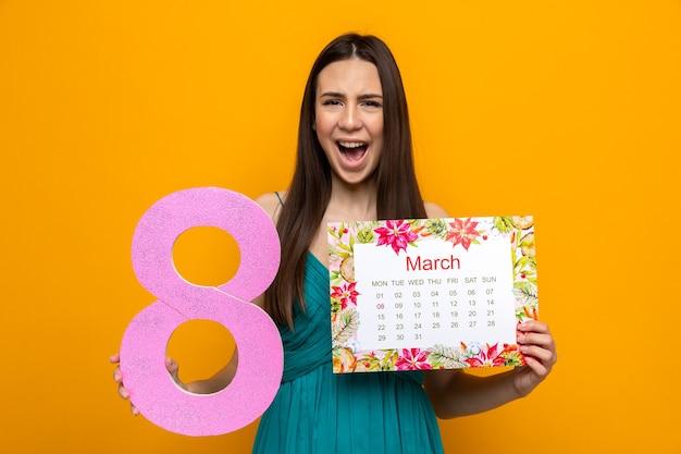 Vrolijk mooi jong meisje op gelukkige vrouwendag met kalender met nummer acht