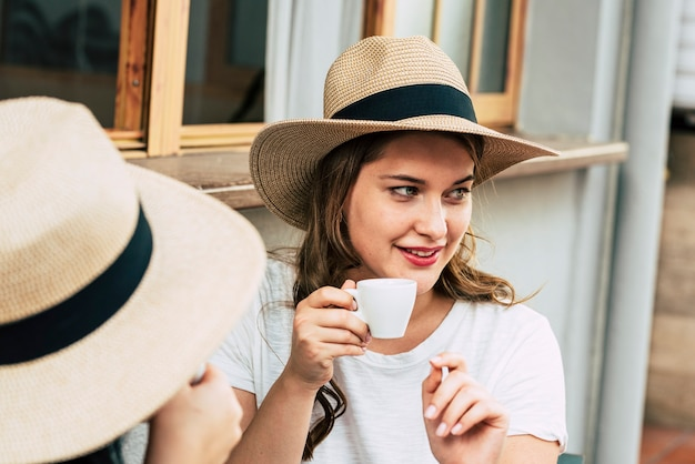 Vrolijk mooi jong vrouwenportret dat koffie drinkt aan de bar met vriend
