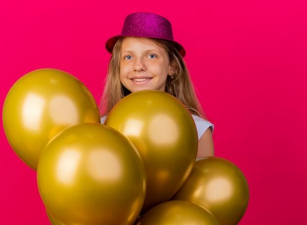 Vrolijk mooi klein meisje in vakantie hoed met bos van baloons kijken camera lachend met blij gezicht, verjaardagsfeestje concept staande over roze achtergrond